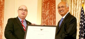 "USCIS Director Emilio T. González presents M.J. Khan with the ""Outstanding American by Choice"" recognition in Washington, DC, Apr. 23, 2007"